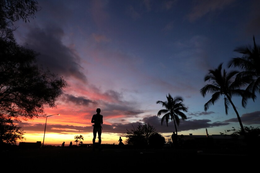 A silhouette of a man on the island of Hawaii at dusk or dawn.