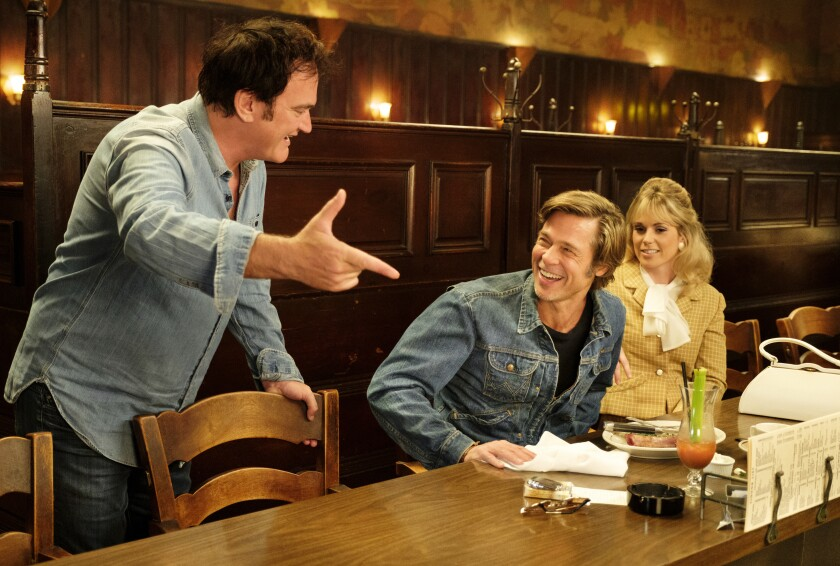 """Quentin Tarantino, left, Brad Pitt and Elise Nygaard Olson on the set of """"Once Upon a Time...In Hollywood."""""""