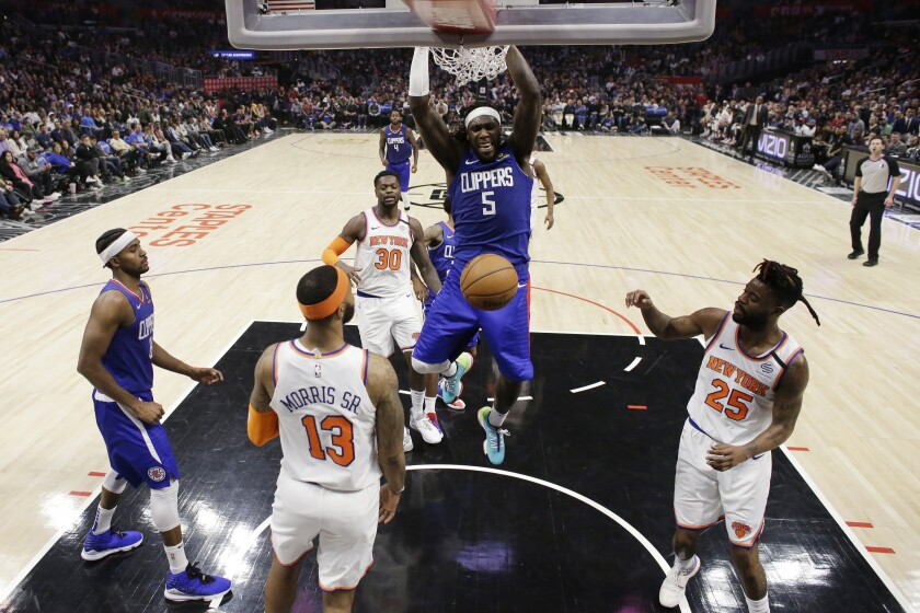 Clippers forward Montrezl Harrell dunks over New York Knicks forward Marcus Morris Sr., left, and guard Reggie Bullock.
