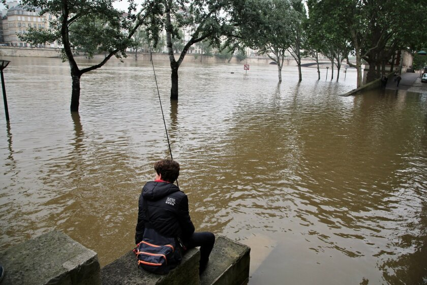 A boy fishes in the Seine river during floods, in Paris, Sunday, June 5, 2016. The riverside Grand Palais exhibition hall in Paris reopened Sunday as floodwaters slowly receded from the French capital, though risks remain for other regions. (AP Photo/Thibault Camus)