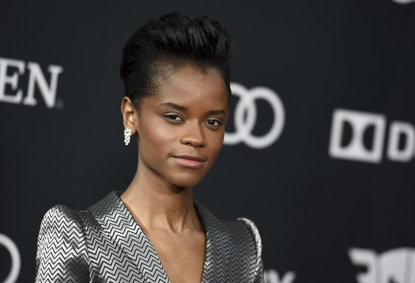 Letitia Wright wearing a striped silver suit