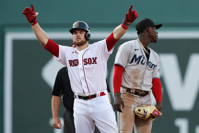 Boston Red Sox's Christian Arroyo, left, reacts beside Miami Marlins' Jazz Chisholm Jr. after hitting a two-run single during the fourth inning of a baseball game, Monday, June 7, 2021, in Boston. (AP Photo/Michael Dwyer)