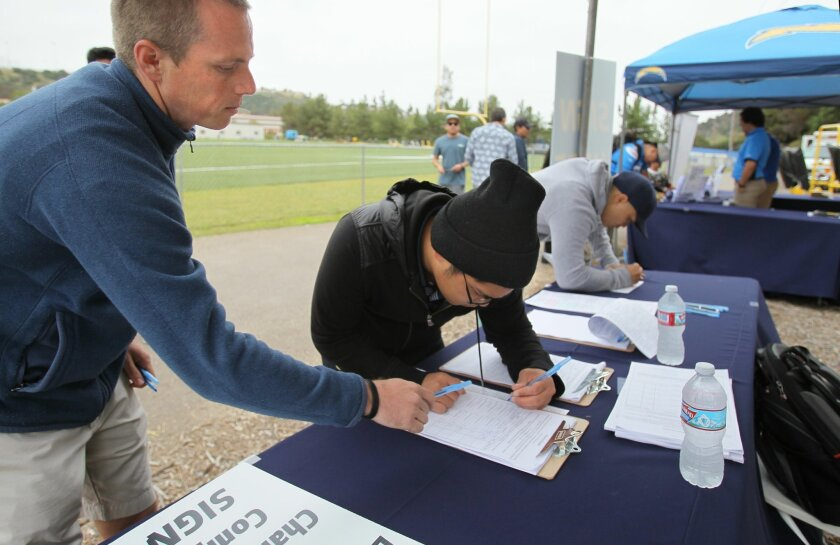 Chargers employee Kellen Arno, left, assists voter Andrew Palmes sign the Chargers stadium ballot initiative petition