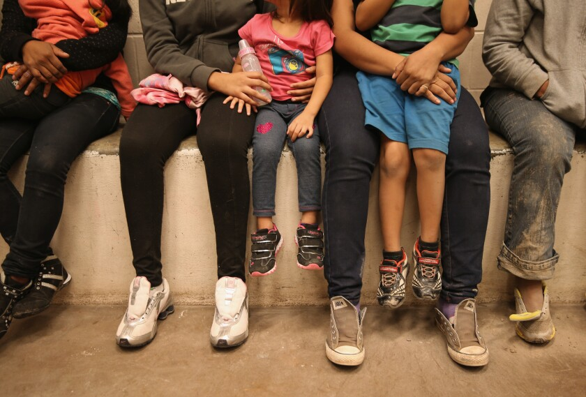 Women and children sit in a holding cell at a Border Patrol processing center