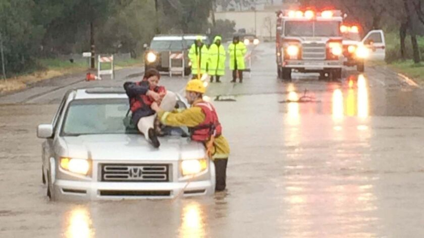Cal Fire/Ramona Firefighter/Paramedic Keith Richards helps a woman whose car stalled in about 3 feet of water on Ramona Street near H Street Monday afternoon.