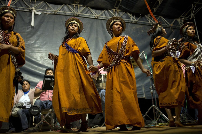 Concursantes de un certámen de belleza asháninka bailan sobre el escenario, en uno de los actos con loa que se celebra la fundación de la comunidad de Otari Nativo.