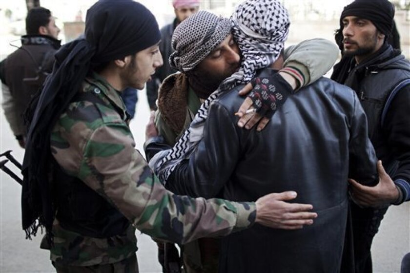 Free Syrian Army fighters console a comrade after an ambulance carried an injured friend to a hospital during fierce fighting against government troops in Idlib, north Syria, Saturday, March 10, 2012. U.N. envoy Kofi Annan met with Syrian President Bashar Assad on Saturday in Damascus during a high