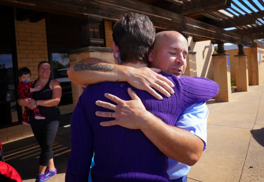 Eric Reyes hugs crash victim Angelique Arenas in front of the Orange Glen Station Post Office in Escondido on Monday.