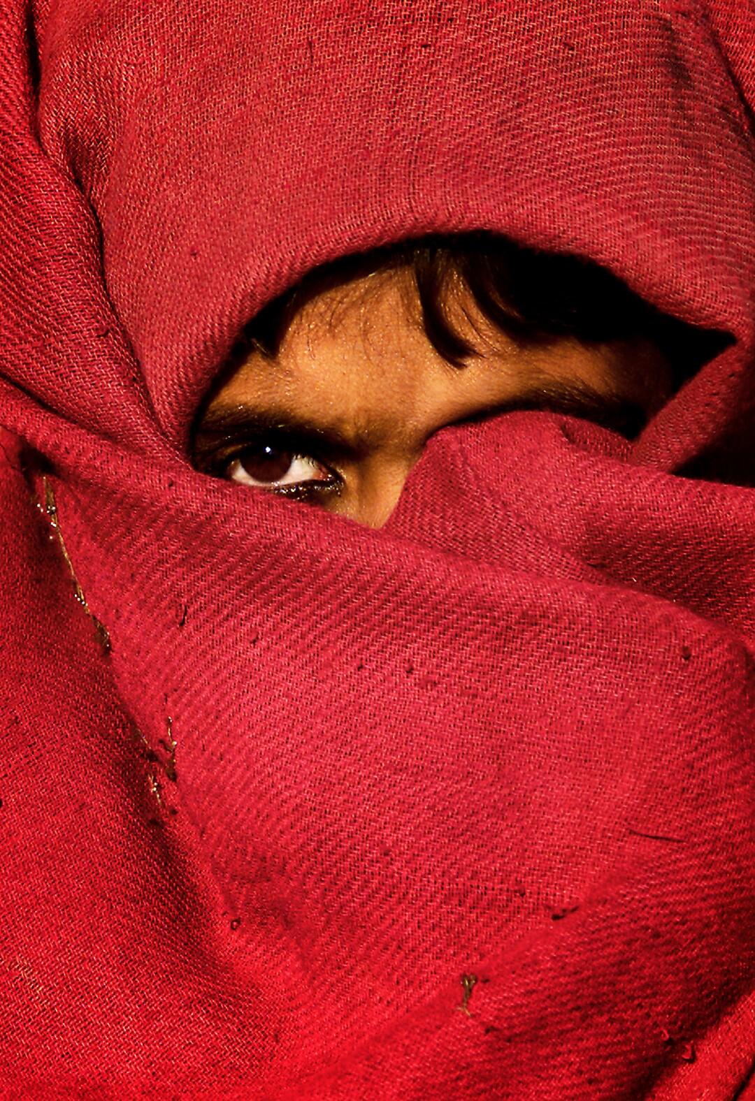 دختری با صورت پوشیده بیشتر با پارچه قرمز