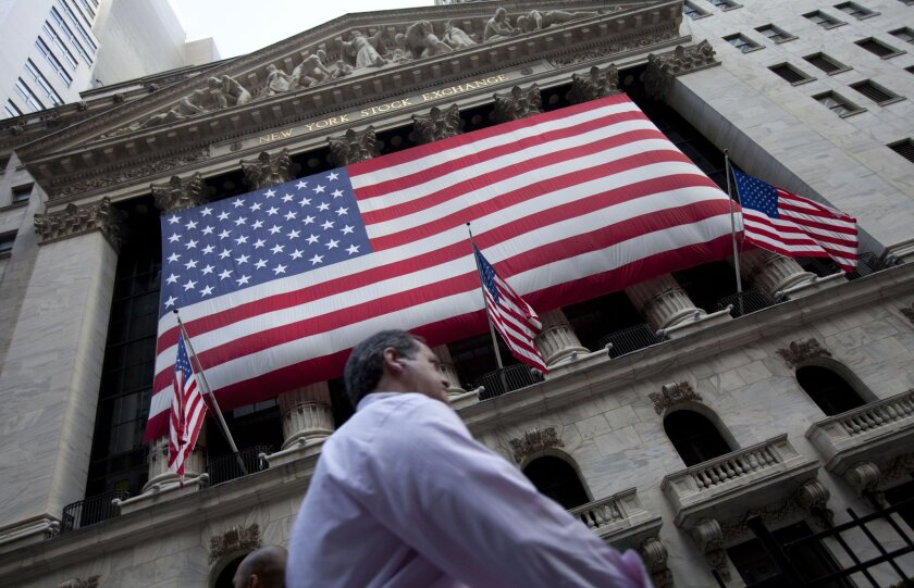 FILE - In this Monday, Aug. 8, 2011 file photo, a pedestrian walks past the New York Stock Exchange in New York. A weak batch of earnings reports is sending the stock market slightly lower in early trading Thursday, April 30, 2015. (AP Photo/Jin Lee, File)