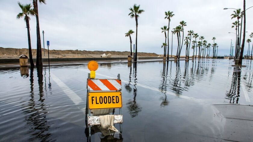 A sign lets visitors know that a beach parking lot near the Balboa Pier in Newport Beach is flooded on Feb. 18.