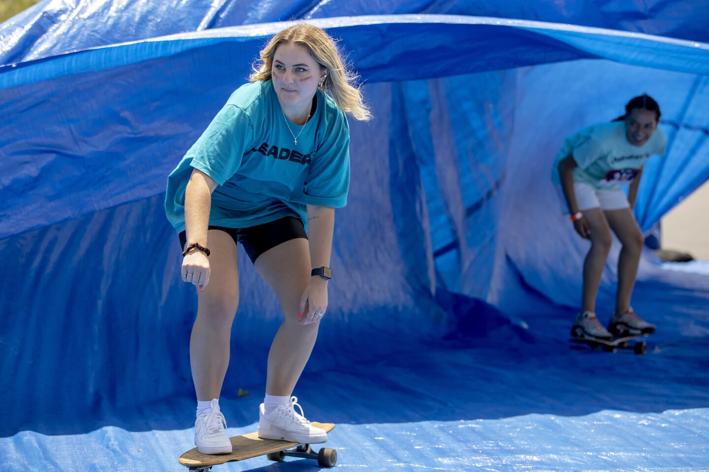 """Competitors skateboard surf during the """"Do Something Church Race"""" on July 31 at Liberty Station."""