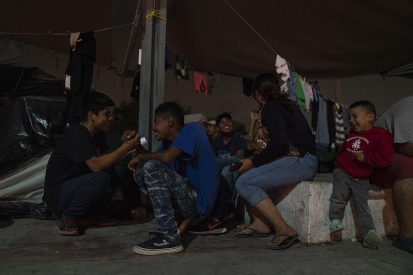 Adolescentes centroamericanos que buscan asilo juegan cerca del Puente Internacional Gateway en Matamoros, México.