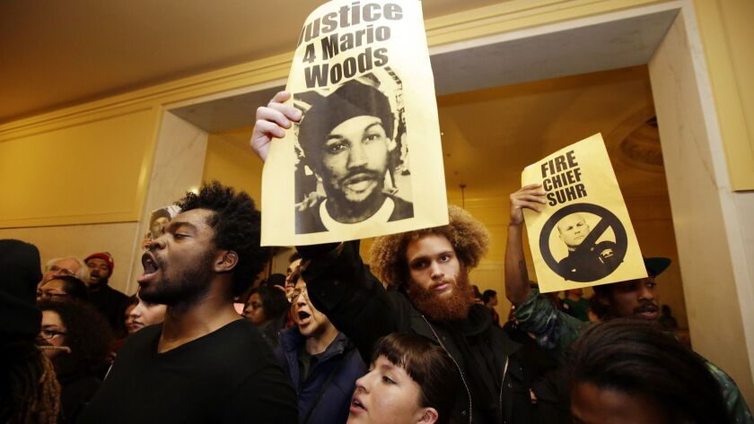 Demonstrators hold signs outside of a crowded police commission hearing inside city hall Wednesday,