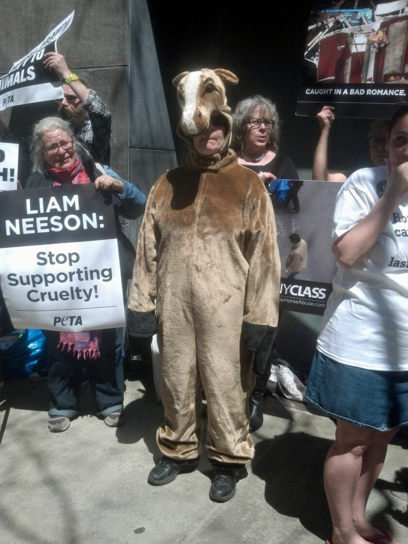 Dressed as a horse, Lisa Jablow, center, a member of NYCLASS which opposes use of carriage horses in New York City, joins other animal rights activists outside actor Liam Neeson's home on Saturday, April 19, 2014 to protest his stance on the continued use of carriage horses in Central Park and certain roads around the city. The 61-year-old actor is a vocal supporter of the city's carriage horse industry. Mayor Bill de Blasio has pledged to ban the horse-drawn carriages and replace them with electric vintage-style cars, commissioned by NYCLASS. (AP Photo/Verena Dobnik)