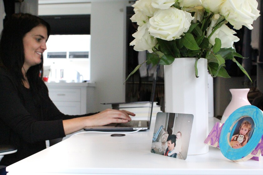 A photo of Kelly Williams of Slate Law Group working from home at a desk in her bedroom