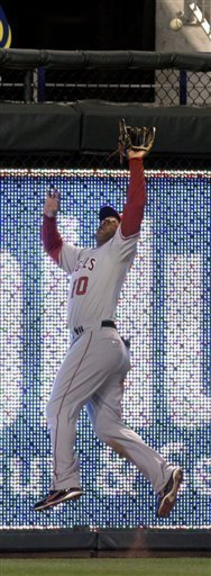 Los Angeles Angels left fielder Vernon Wells jumps to catch a fly ball hit by Kansas City Royals' Jeff Francoeur during the sixth inning of an MLB baseball game Friday, April 1, 2011 in Kansas City, Mo. (AP Photo/Charlie Riedel)