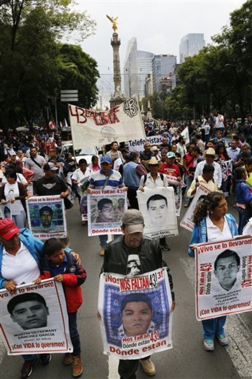 Familiares de los 43 estudiantes desaparecidos cargan fotos de sus seres queridos durante una marcha para exigir que sean hallados y se haga justicia en una de las mayores violaciones a los derechos humanos ocurridas en la historia reciente del país. La manifestación, con motivo del segundo aniversario de esos hechos, se realizó en Ciudad de México el lunes de 26 de septiembre del 2016.