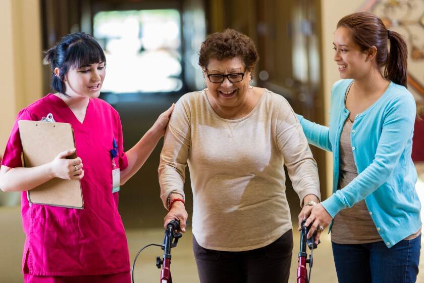 Confident physical therapist assists senior woman in assisted living facility