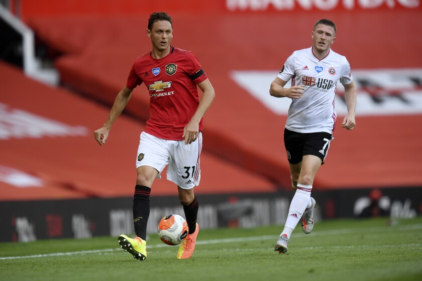 Manchester United's Nemanja Matic, left, passes the ball during the English Premier League soccer match between Manchester United and Sheffield United at Old Trafford in Manchester, England, Wednesday, June 24, 2020. (Michael Regan/Pool via AP)