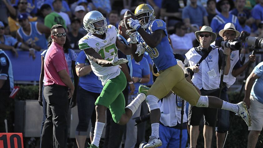 UCLA defensive back Colin Samuel, right, intercepts a pass intended for Oregon's Dillon Mitchell during a game at the Rose Bowl in October.