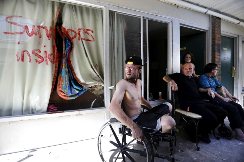 Wes Allen, Jr., from left, sits with his father Wes Allen, Sr., sister Alison, and mother Vicki outside their room at a damaged motel in Panama City, Fla., where many residents continue to live in the aftermath of Hurricane Michael.