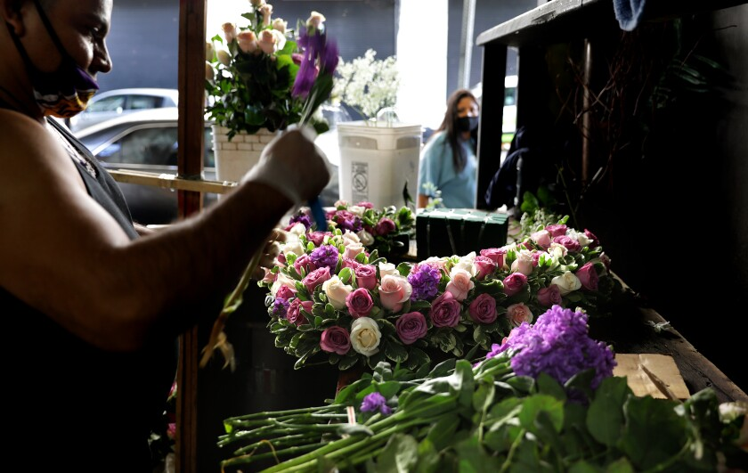 Jaime Miranda creates an arrangement at Lupita's Flowers in downtown Los Angeles on Wednesday. Flower wholesalers have already been allowed to reopen and other select retailers can open Friday.
