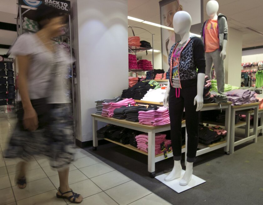 In this Tuesday, Aug. 19, 2014 photo, a woman passes an active wear display at a J.C. Penney store, in New York. The Commerce Department releases retail sales data for August on Friday, Sept. 12, 2014. (AP Photo/Richard Drew)