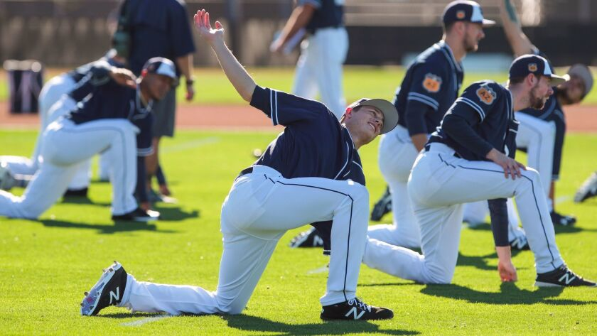 Padres relief prospect Phil Maton, center, and other pitchers and catchers stretch during the first official workout for catchers and pitchers at the Peoria Sports Complex in Peoria, Ariz.