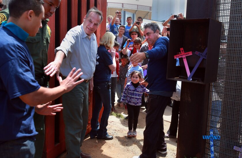 Mayor Bob Filner reaches for Luis Angulo (left), while Enrique Morones of the Border Angels directs Angulo's daughter Ximena, 5, on the Mexico side. The gate at Friendship Park opened on Sunday for just a few minutes. Peggy Peattie • U-T