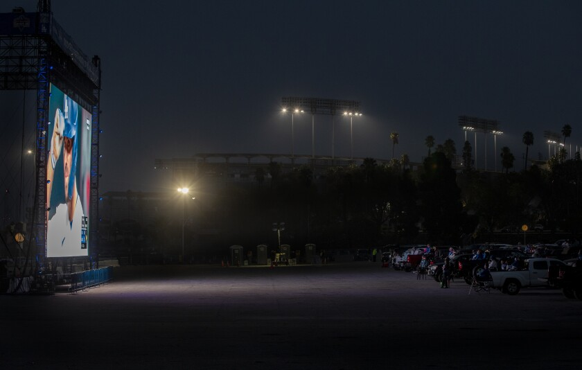 Cars are parked in front of a giant screen at Dodger Stadium