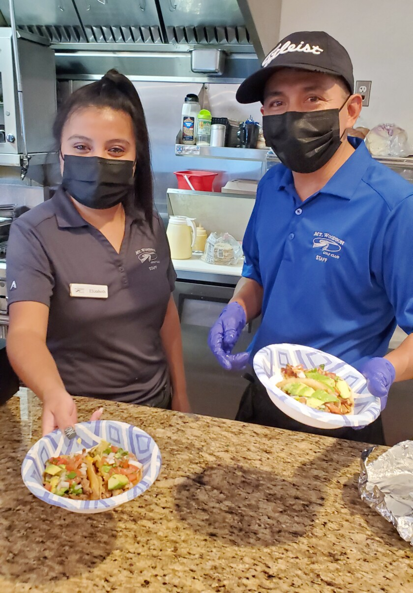 Stony Mountain Bar & Grill server Elizabeth Ortiz, left, and chef Hilario Garcia serve up one of their specialties.