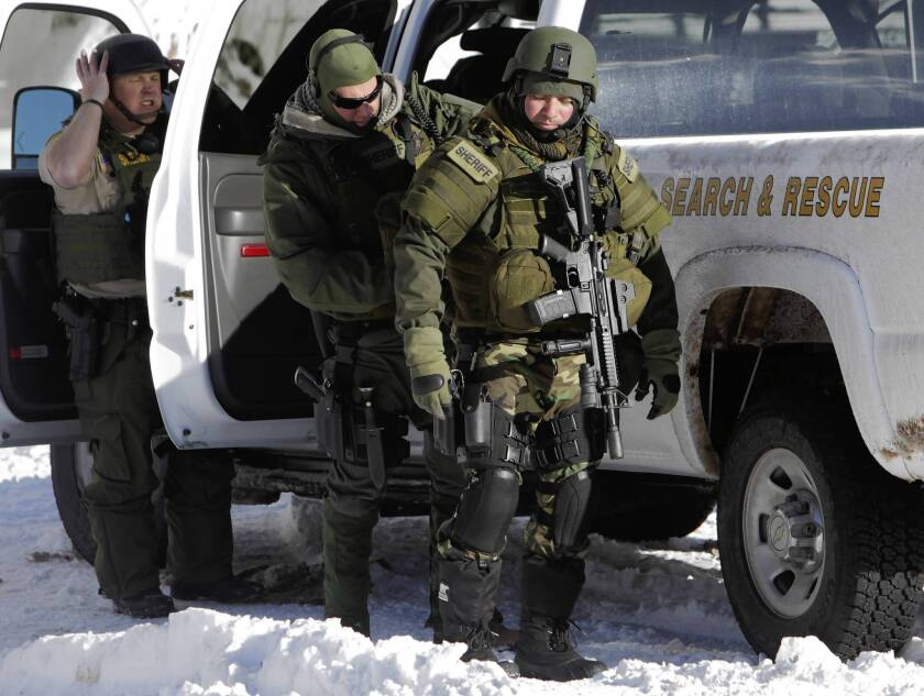 Search and rescue personnel from the San Bernardino County Sheriff's Department gear up for the continuing manhunt for fugitive ex-cop Christopher Dorner in the mountains around Big Bear Lake.