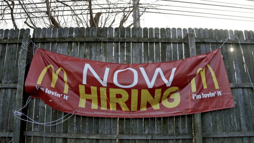 FILE- In this Jan. 3, 2019, file photo an employment sign hangs from a wooden fence on the property