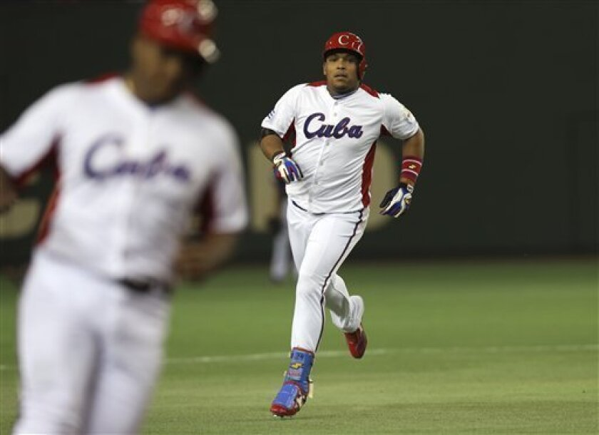 Cuba's rightfielder Yasmany Tomas, right, rounds bases after hitting a three-run homer off Taiwan's pitcher Yang Yao-hsun in the fourth inning of their World Baseball Classic second round game at Tokyo Dome in Tokyo, Saturday, March 9, 2013. At left rounding third base is teammate Alfredo Despaigne