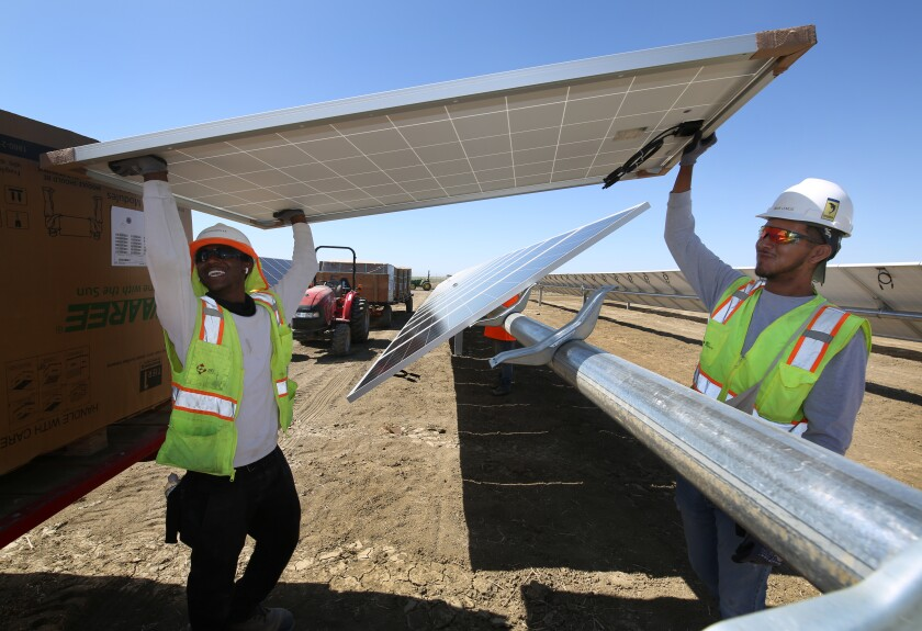 From left to right, construction workers Rayshawn Lee and Omar Lemus place panels at Westlands Solar Park.
