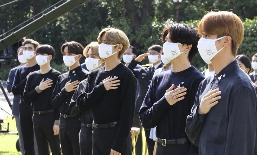 La banda sudcoreana BTS saluda su bandera nacional durante una ceremonia