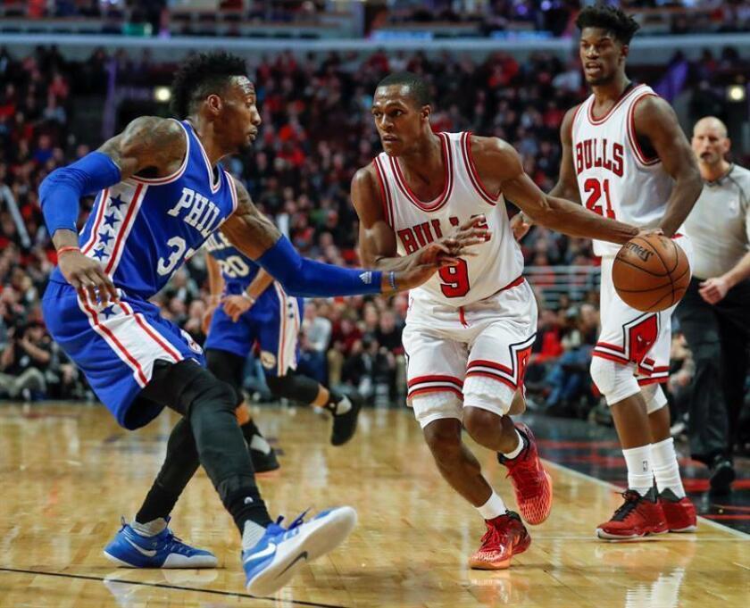 Robert Covington (i) de los 76ers ante Rajon Rondo (c) de los Bulls, en un momento del partido que ambos equipos han disputado esta noche en el United Center de Chicago, Illinois. EFE