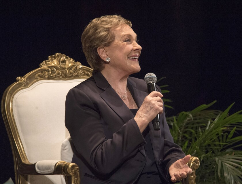 Julie Andrews, smiling and holding a microphone, seated onstage at the Orpheum.