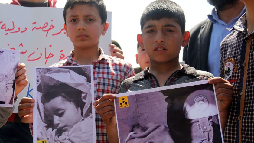 In this photo taken on April 7, Syrian residents of Khan Sheikhun hold up placards and photographs during a protest condemning a suspected chemical weapons attack on their town that killed at least 86, including 30 children.