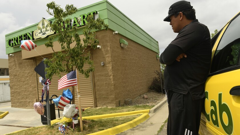 Cab driver Juan Molina pays his respects to Travis Mason, a pot store security guard who was killed by would-be robbers in Aurora, Colo., last month.