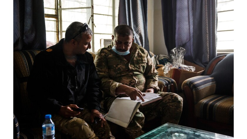 Maj. Tarek Gazali, left, is briefed by a fellow medic on civilian injuries treated at a field clinic operated by medics from the Iraqi Emergency Response Division and NYC Medics.