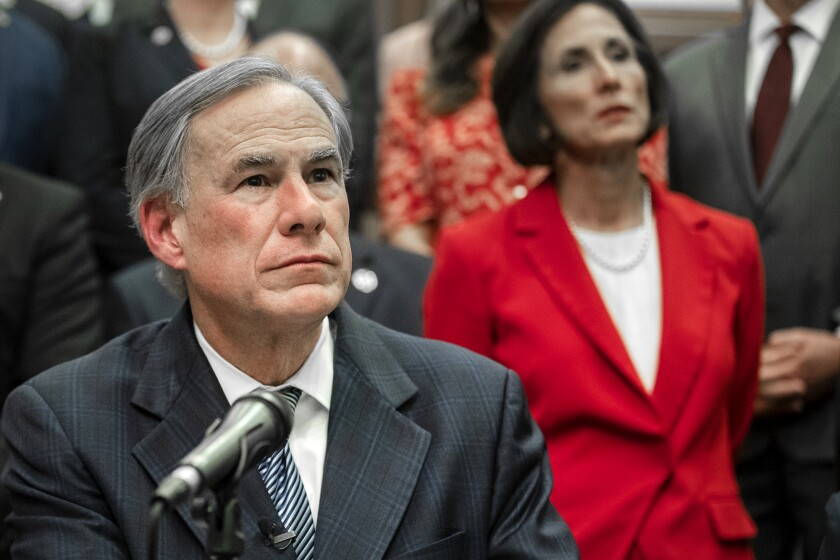 A man sits near a microphone with people behind him