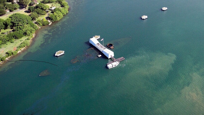 The USS Arizona Memorial, a monument to those who died, floats above the submerged battleship, clearly visible in this June 27, 2016, photo. Oil, which continues to seep from the ship, creates a continual slick in the water.