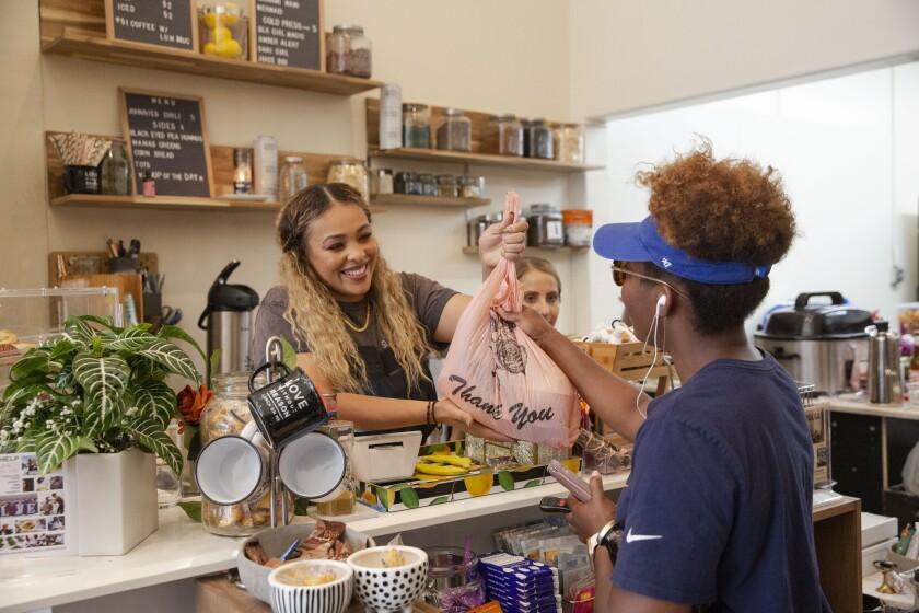 LaRayia Gaston hands groceries to customer Kendall Young at LaRayia's Bodega.