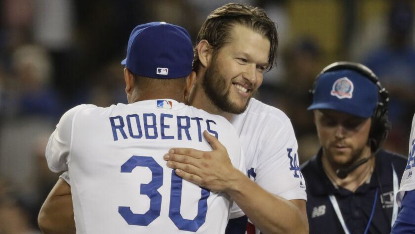 Clayton Kershaw embraces Dodgers manager Dave Roberts as the team celebrates a 3-0 victory over the Braves in Game 2 of the National League Divisional Series at Dodger Stadium.