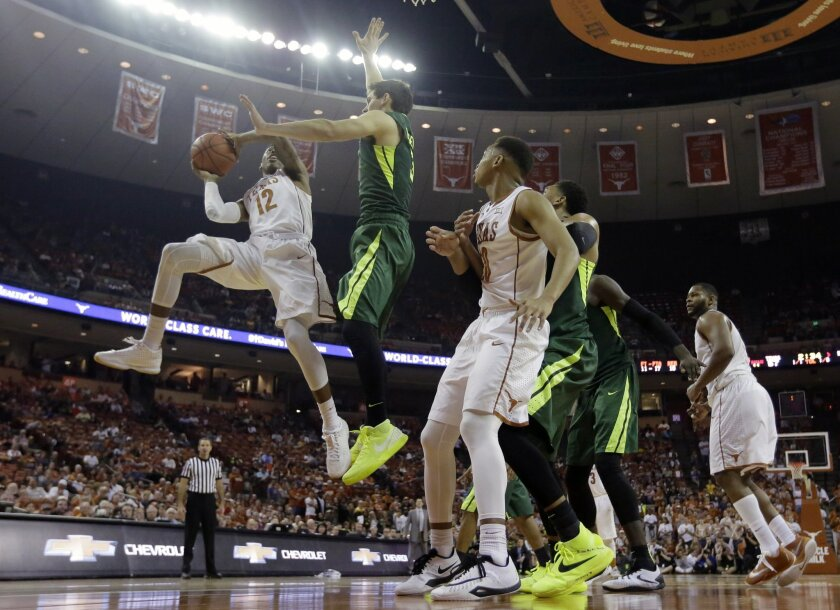 Texas guard Kerwin Roach Jr. (12) is blocked by Baylor guard Jake Lindsey (3) as he drives to the basket during the second half of an NCAA college basketball game, Saturday, Feb. 20, 2016, in Austin, Texas. Baylor won 78-64.(AP Photo/Eric Gay)