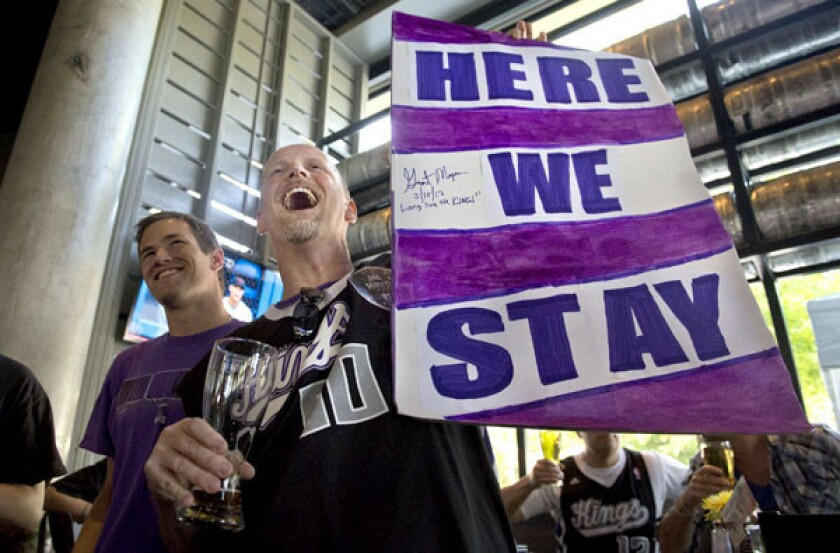 """Kings fan Kris Haskins holds a """"Here We Stay"""" sign after hearing the NBA owners rejected the franchise's move to Seattle on Wednesday."""