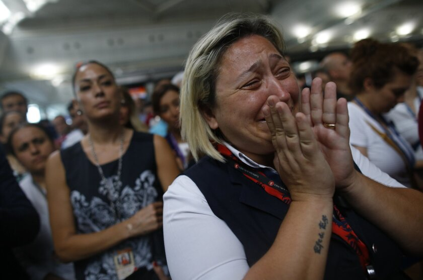 A woman reacts as Family members, colleagues and friends of the victims of Tuesday blasts gather for a memorial ceremony at the Ataturk Airport in Istanbul, Thursday, June 30, 2016. A senior Turkish official on Thursday identified the Istanbul airport attackers as a Russian, Uzbek and Kyrgyz nation