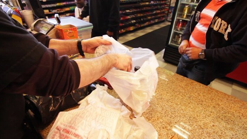 A customer in San Diego receives purchased items in a plastic bag.